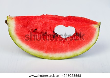 Slice of fresh watermelon with symbol of heart in it - stock photo