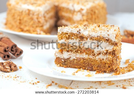 Slice of gourmet carrot cake with walnut crumbs and cinnamon on white plate - stock photo