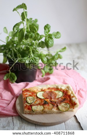 Slice of homemade pizza with tomato sauce, zucchini, spicy salami, mozzarella and basil leaves. On white rustic table, decorated with checkered tablecloth and basil pot. Selective focus. - stock photo