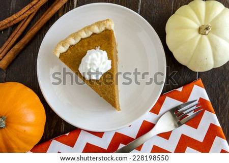 Slice of homemade pumpkin pie with whipped cream sitting on white plate with small pumpkins, cinnamon sticks and fork on orange chevron napkin - stock photo