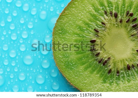 Slice of kiwi with drop on blue background - stock photo