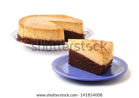 Slice of layered chocolate Mexican flan on plate next to whole pie on white background - stock photo