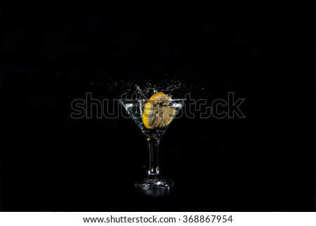 slice of lemon dropped in a glass with a cocktail on a dark background - stock photo