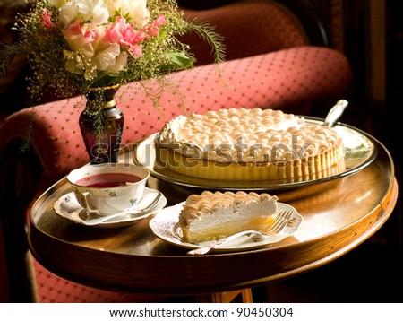 Slice of lemon meringue pie with cup of tea, selective focus - stock photo