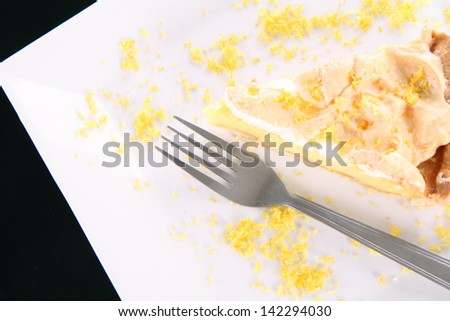 Slice of Lemon Meringue Tart decorated with lemon peel on a plate on black background - stock photo