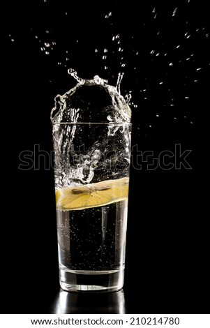 Slice of lemon splashing into a glass of water with a spray of water droplets in motion suspended in the air above the glass on a dark background.