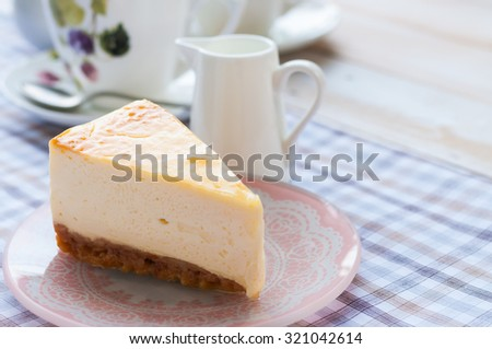 Slice of new york style cheesecake with a cup of tea