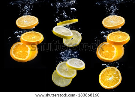 slice of orange and lemon in the water with bubbles, on black background - stock photo