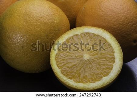 Slice of orange and whole oranges/Orange Slice/Bunch of oranges and a slice orange on a black surface - stock photo
