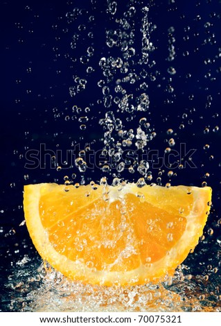 Slice of orange with stopped motion water drops on deep blue - stock photo