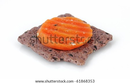 Slice of pickled carrot on top of a rice cracker.
