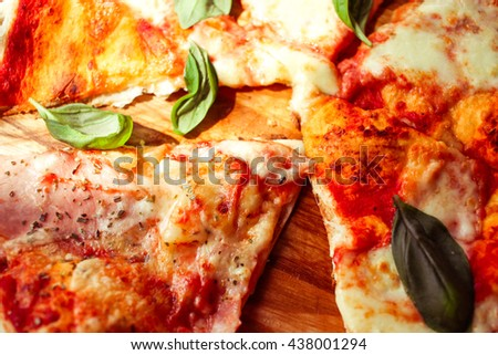 Slice of pizza with cheese and spices close up on scratched wooden table