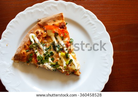 Slice of pizza with mayonnaise on plate detail. Wooden table - stock photo