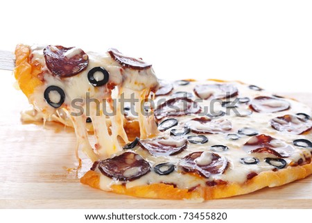 Slice of pizza with salami, black olives and melted cheese. - stock photo