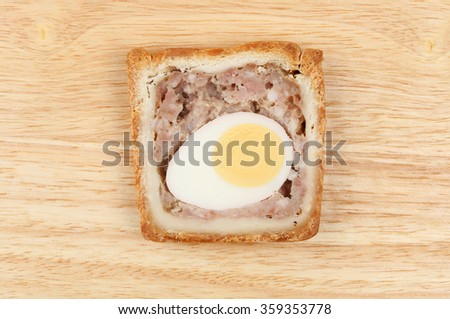 Slice of pork and egg gala pie on a wooden board