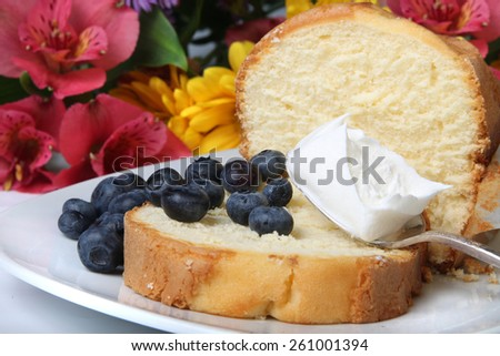 Slice of pound cake with blueberries and  spoon topped with whipped cream  and flowers in the background - stock photo