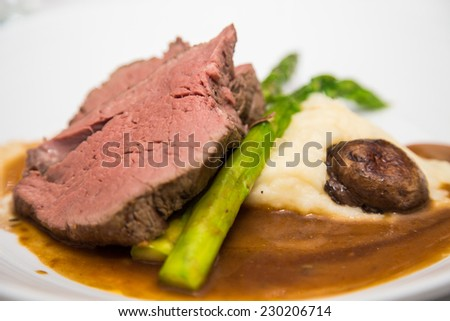Slice of prime rib on asparagus with gravy, mushroom and mashed potatoes - stock photo