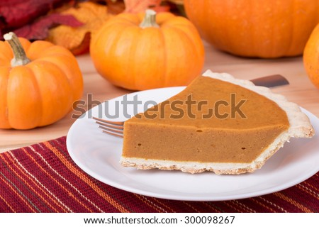 Slice of pumpkin pie with pumpkins in background