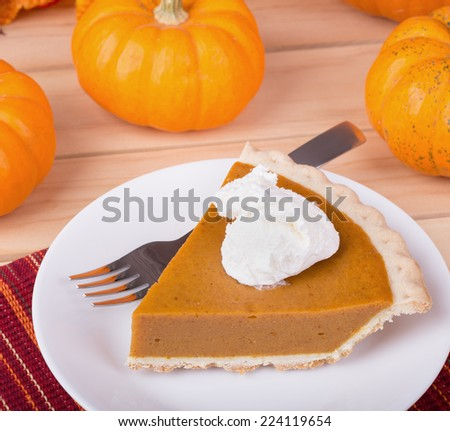 Slice of pumpkin pie with whipped cream and pumpkins in background - stock photo