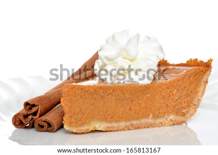 slice of pumpkin pie with whipped topping and cinnamon sticks isolated on white background