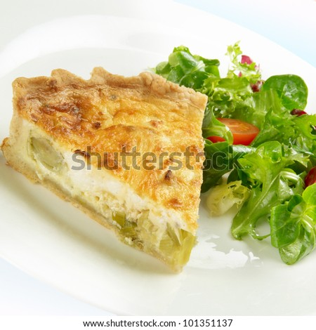 Slice of quiche made from leek and goats cheese, on a plate with leaf salad