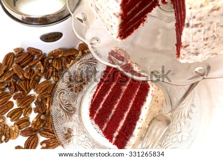 Slice of red velvet cake and pecans with sugar canister in background.  Slice is removed from whole cake which is in background.  Fork is on plate. - stock photo