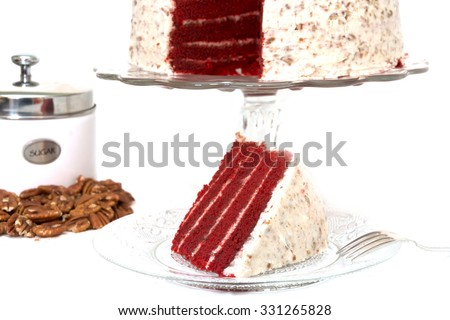 Slice of red velvet cake removed from whole cake which is in background along with sliced pecans and sugar canister.  Slice of cake is on plate along with fork.  Isolated on white background.