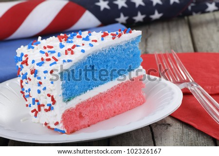 Slice of red white and blue cake with american flag in background