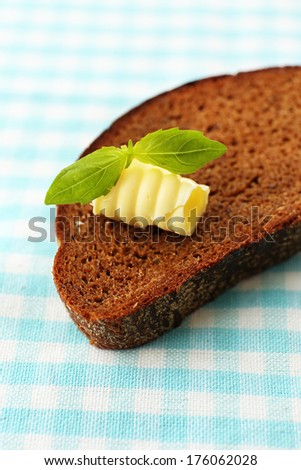 Slice of rye bread with butter, on tablecloth
