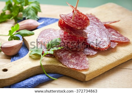 Slice of salami sausages on wooden board