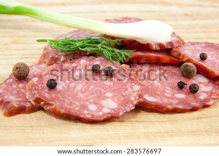 Slice of salami sausages on wooden board isolated