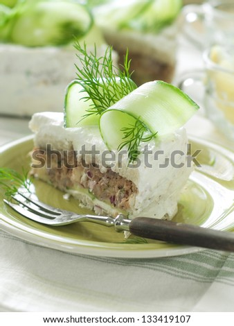 Slice of sandwich cake with tuna and cucumber, selective focus