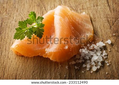 Slice of smoked salmon with sea salt and parsley - stock photo