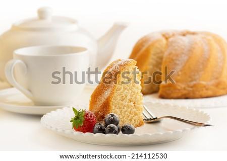 slice of sponge cake and white porcelain - stock photo