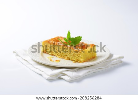 slice of sponge cake with almond flakes and mint on white plate and place mat