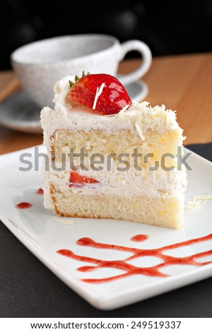 Slice of strawberry shortcake with white chocolate shavings