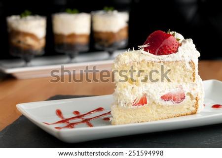 Slice of strawberry shortcake with white chocolate shavings. - stock photo