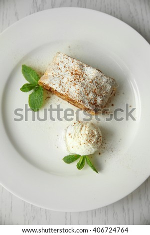 Slice of strudel with apples, walnut, raisins and ice cream ball on white plate - stock photo