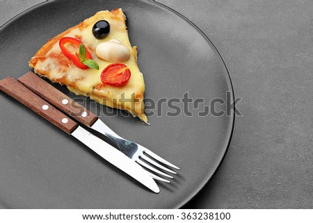 Slice of tasty pizza with knife and fork on black plate, close up - stock photo