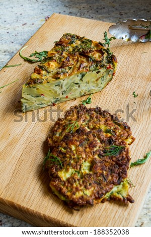 Slice of thick tortilla (omelette, frittata) made with potato, lettuce, chili and free-range eggs. Courgette fritter in the foreground. - stock photo