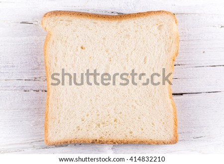 slice of toast on white wooden background, closeup, textured - stock photo