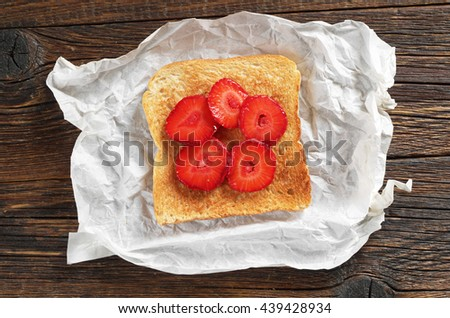 Slice of toasted bread with strawberries on crumpled paper on table, top view - stock photo