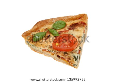 Slice of tomato and basil quiche with garnish isolated against white