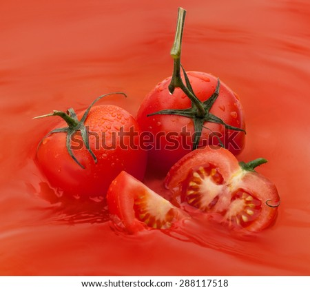 slice of tomato and two tomatoes in juice - stock photo