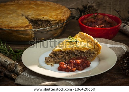 Slice of traditional pork meat pie Tourtiere with apple and cranberry chutney from Quebec, Canada. - stock photo