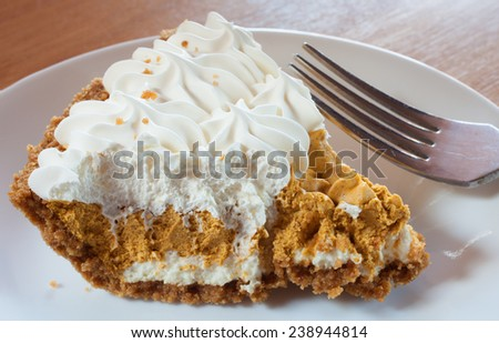 Slice of whipped pumpkin pie that has white frosting