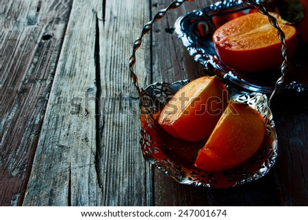 Slice persimmon on rustic wooden background. Selective focus. - stock photo