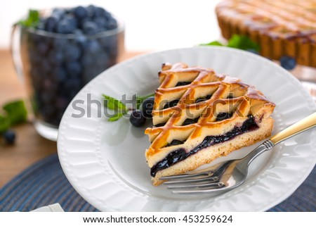 Slice piece of berry blueberry tart pie golden crust holiday dessert - stock photo