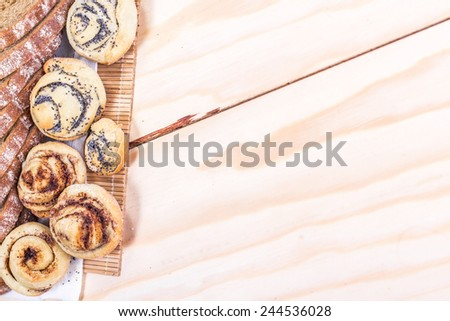 slice wheat bread and sweet buns on wooden table