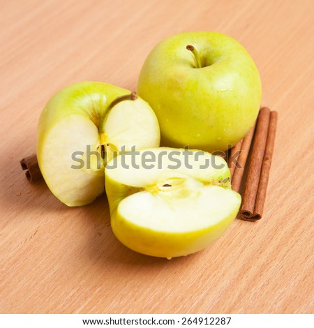 sliced apples and cinnamon sticks on wooden background